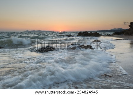 Big wave and the rock with sunset sky at Rayongbeach, Thailand. - stock photo