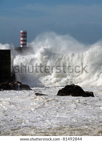 Big wave in the mouth of river Douro in Portugal seeing part of the wall and one of the beacons - stock photo