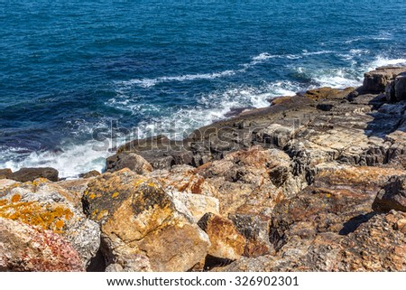 Big wave splash. Sea water beating against the rocks and cliffs. Blue sky above the beach in the sun zenith refreshing drops of water of the ocean. As background for the design of stage - stock photo