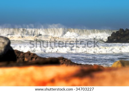 Big Wave stormy ocean waves with drift wood in the foreground. - stock photo
