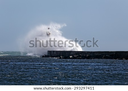 Big waves against beacon and pier of Ave river mouth, Vila do Conde, Portugal - stock photo