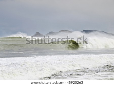 Big waves breaking in the coast, with some mountains in the background. Extreme surf area - stock photo