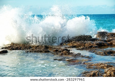 Big waves breaking on the shore with sea foam - stock photo