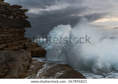 Big waves crashing against the cliffs at Clovelly NSW Australia - stock photo