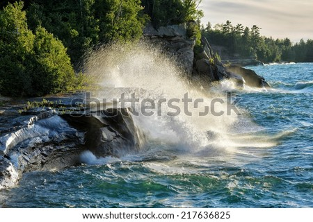 Big waves crashing on the rocky lake superior shoreline Michigan's Upper Peninsula - stock photo