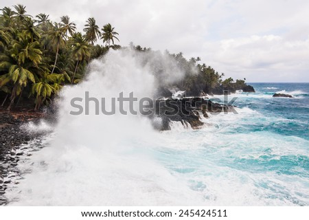 Big waves crushing on the shore of a tropical island with palm trees during a storm. Praia Piscina - Sao Tome and Principe. - stock photo