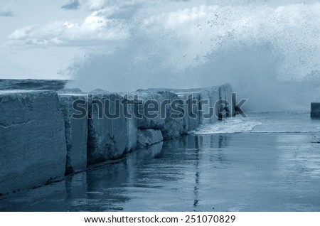 big waves impact the cliff over the pier - stock photo