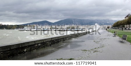Big waves on the lake of Geneva going through the wall on the lakeside by cloudy and rainy day in Geneva, Switzerland - stock photo