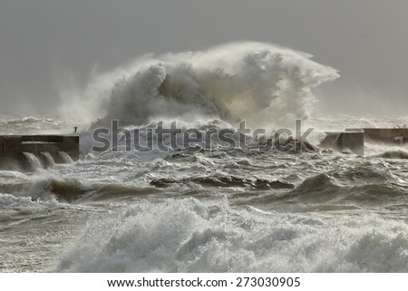Big waves over pier from the portuguese north coast in a stormy afternoon