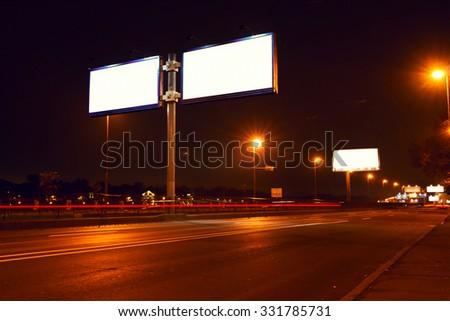 Big white billboard on lighting street at night - stock photo