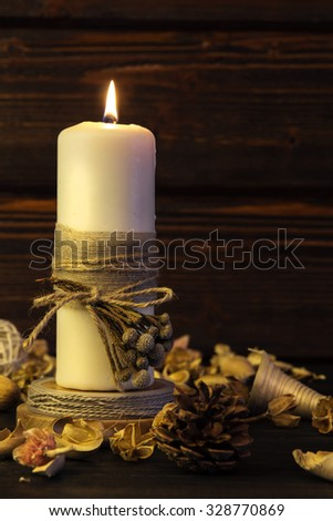 Big white candle on rustic wooden background.