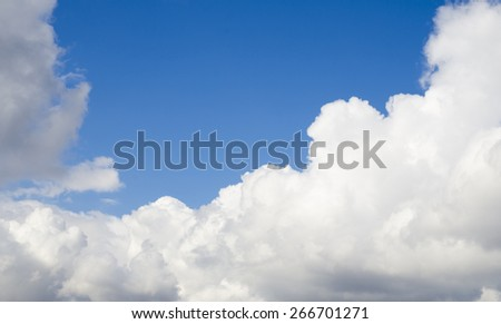 Big white fluffy clouds flying in the deep blue spring sky - stock photo