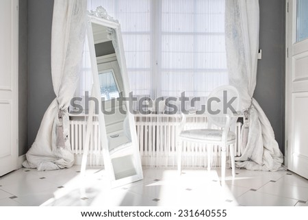 Big white mirror in the middle of luxury white room - stock photo