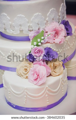 Big white multilevel wedding cake with roses and decorative flowers on it