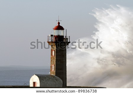 Big white ocean wave against Lighthouse e Pier of Porto in a stormy morning - stock photo