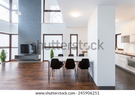Big white table in spacious lounge with wooden floor - stock photo