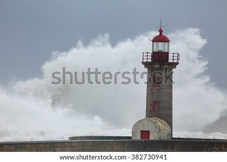 Big white wave over old lighthouse and granite pier, north of Portugal - stock photo
