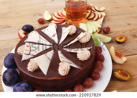 big whole frost chocolate cream brownie cake topped with white chocolate and cream flowers with hot tea cup decorated with fruits apple plum and grape on plate on wooden table - stock photo