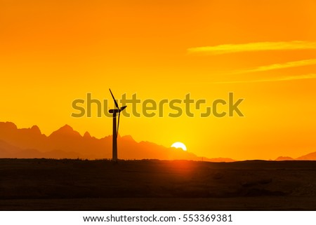 Big wind turbines in the desert against mountains