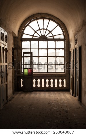 Big window at the end of a hallway in deserted colonial house - stock photo