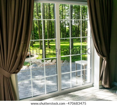 Big window with view of summer backyard