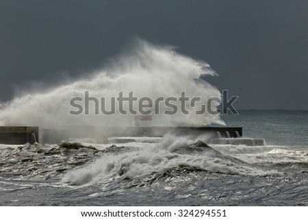 Big windy waves over pier and beacon of the river Douro mouth harbor