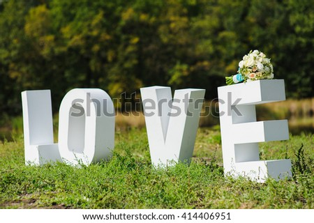 Big wood white letters Love letters on a background of green park. Beautiful wedding bouquet tied with white lace and blue ribbon on big e letter. Forest and river in the background. - stock photo