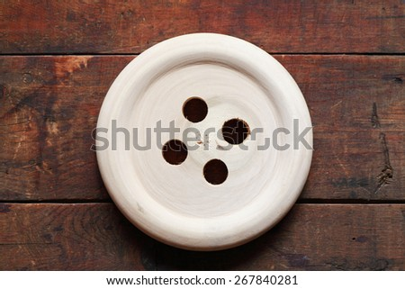 Big wooden button on nice old wood background - stock photo