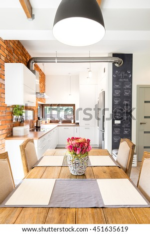 Big wooden dining table set for family dinner. In the background modern kitchen