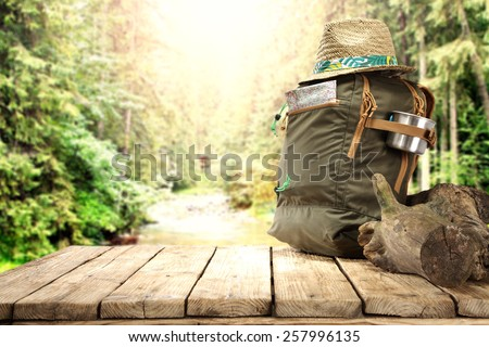 big wooden table of free space and backpack with hat  - stock photo