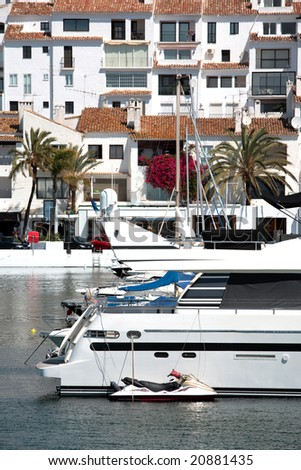 Big Yachts and Jet Bike in Puerto Banus Harbour with Traditional Spanish Architecture in the Buildings - stock photo