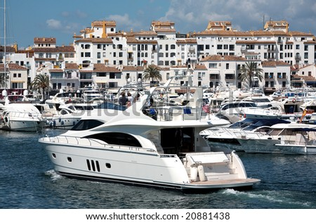 Big Yachts in Puerto Banus Harbour with Traditional Spanish Architecture in the Buildings - stock photo