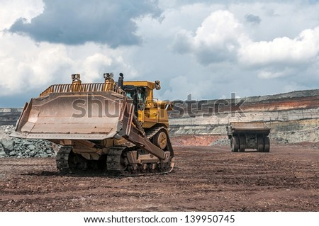 big yellow excavator and mining truck at work site - stock photo
