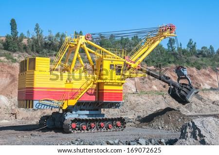 big yellow excavator extracting iron ore in opencast mine - stock photo