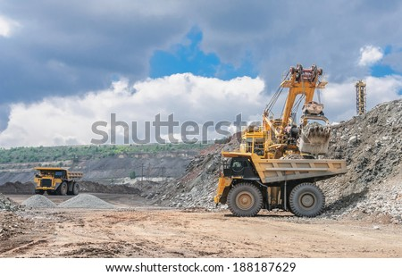 big yellow excavator extracting iron ore in opencast mine and loading heavy truck