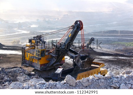 Big yellow mining truck working at worksite - stock photo