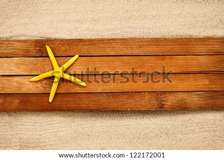 Big yellow seastar on a wooden boards against sandy background. - stock photo
