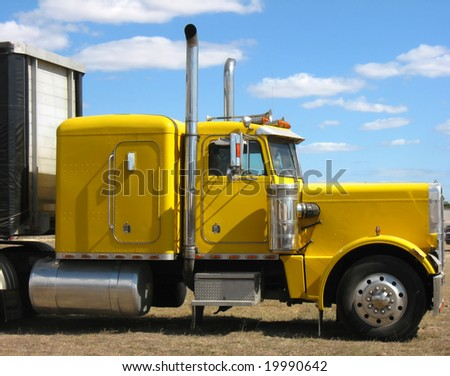 big yellow truck against blue sky - stock photo