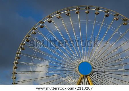 big yellow wheel at the local fair against blue cloudy background