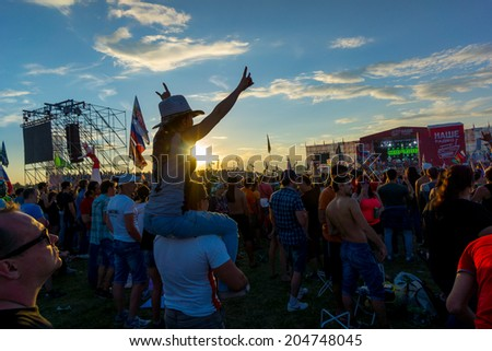 "BIG ZAVIDOVO, RUSSIA - JULY 5: People cheering at open-air rock festival ""Nashestvie"" on July 5, 2014 in Big Zavidovo, Russia. ""Nashestvie"" is the biggest rock festival in Russia, more 200000 visitors - stock photo"