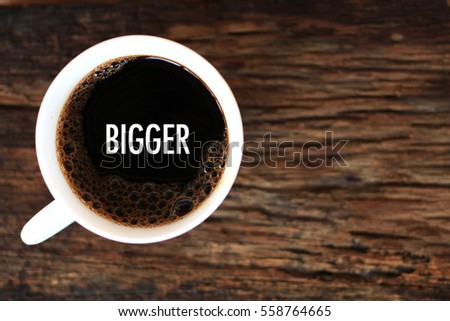 BIGGER - business concept of coffee cup on wooden background
