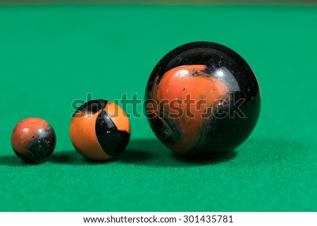 Bigger to smaller black and orange Marble Balls on green background - stock photo