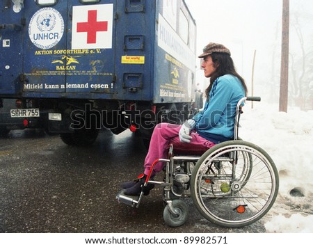 BIHAC, BOSNIA - NOV 19: A wheelchair bound man, wounded in fighting between Muslim and Serbian forces, sits beside a truck carrying food and medicine aid outside of Bihac, Bosnia, on Tuesday, November 19, 1995. - stock photo