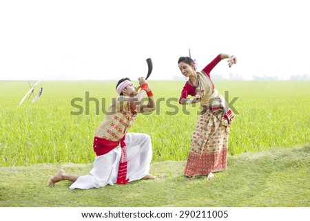 Bihu man blowing on a pepa while Bihu woman dances to his tune - stock photo