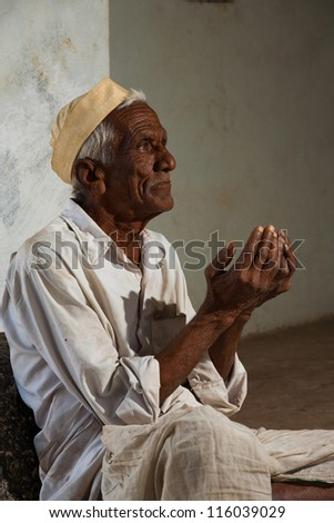 Bijapur, India - February 19, 2009: Profile of Indian male wearing white begging with his cupped hands out asking for change at the entrance of a mosque