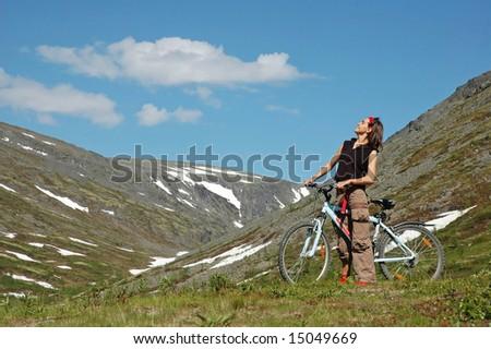 Bike adventure! Girl biking in the mountains. - stock photo