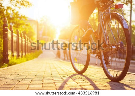 Bike at the sunset on the tiled road in the city park. Cycle closeup rear wheel on blurred background. Cycling down the street at summer sunset. Bicycle and lifestyle concept.