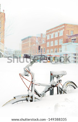 Bike buried in snow, city buildings in background - stock photo