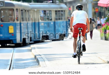 Bike commuter and tram in sunlit city