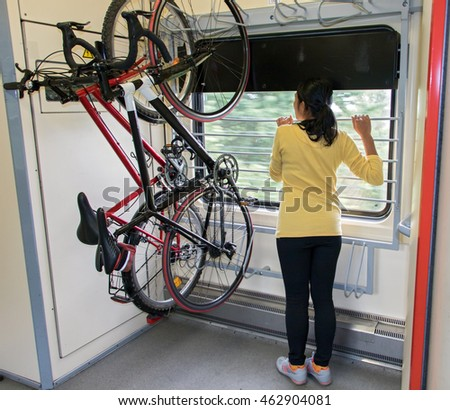 Bike hanging on the rack in the train. Transport bicycles in the wagon.Woman traveling on a train with a bicycle.